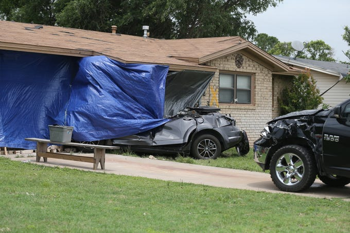 Two vehicles on 24th Street in San Angelo were heavily damaged and one of them slammed into the house during a tornado that hit town Saturday, May 18, 2019.<br /> Charles Bryce/San Angelo Standard-Times