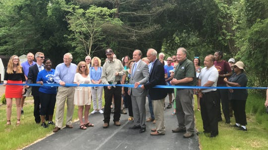 Officials cut a ribbon to ceremonially mark completion of the second phase of the Southern Tip Bike and Hike Trail near Capeville, Virginia on Friday, May 17, 2019.