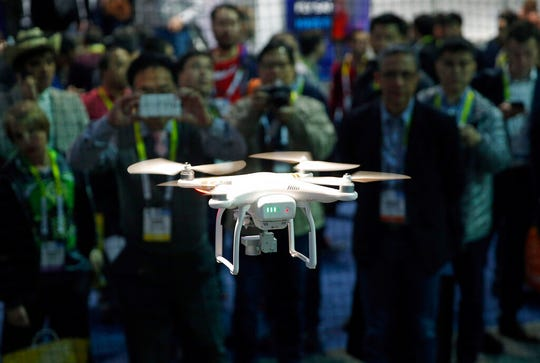 FILE - In this Jan. 7, 2016 file photo, a drone hovers at the DJI booth during CES International in Las Vegas. In Utah, drones are hovering near avalanches to measure roaring snow. In North Carolina, they're combing the skies for the nests of endangered birds. In Kansas, meanwhile, they could soon be identifying sick cows through heat signatures. A survey released Monday, May 20, 2019 shows transportation agencies are using drones in nearly every U.S. state. (AP Photo/John Locher, File)