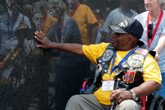 Darryl Stewart, 68, a Vietnam War veteran who served in the Navy, runs his hand across the portraits etched into marble at the Korean War Memorial Saturday, May 18, 2019. Stewart attended Honor Flight Tallahassee, which allows veterans to travel to the Washington, D.C., area to visit the various memorials.
