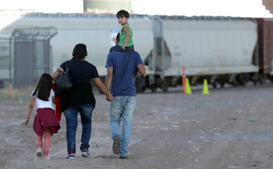 A Brazilian family walks to border agents as they surrender to seek asylum in the United States on Thursday, May 16, 2019. The migrant flow across this section of border near El Paso's Chihuahuita neighborhood has been heavy.