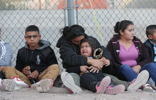 A young girl cries in her mother's arms as they are processed on the border by U.S. Border Patrol agents on Thursday, May 16, 2019.