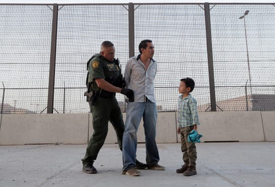 Jose Jr. looks up at his father Jose as he is searched by Border Patrol Agent Frank Pino after crossing into the United States to seek asylum.