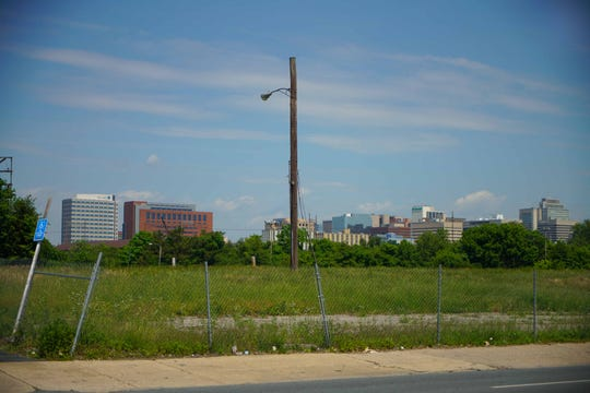 Downtown Wilmington looms over a vacant lot in the low-income neighborhood of Southbridge. Both areas have been designated for investment through a program offering lucrative federal tax breaks.