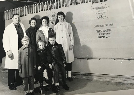 The Leo and Virginia Krohn family stand by the world's largest cheese made by Steve's Cheese in Denmark for the 1964 World's Fair with milk from Krohn's Dairy - a total of 170,000 quarts of milk. The cheese weighed a whopping 34,591 pounds. Joining them from left in the back row is Sandra and Jean Krohn. Front row from left, Sue, Carl and Roger Krohn.