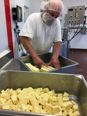 Terry Woods cuts cheese curds at Highfield Farm Creamery in Walworth. Small batches of cave-aged cheeses are made from the milk of pasture-raised Jersey cows.