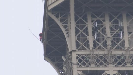 A rescue worker attempts to contact a man who tried to climb the Eiffel Tower.