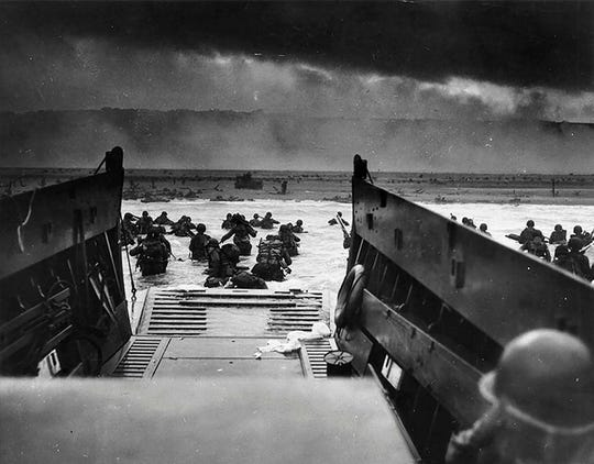 (FILES) This picture taken on June 6, 1944, shows U.S. Army troops wading ashore at Omaha Beach in north-western France, during the D-Day invasion. The 75th anniversary of the D-day landings will fall on June 6, 2019. (Photo by National Archives / AFP)