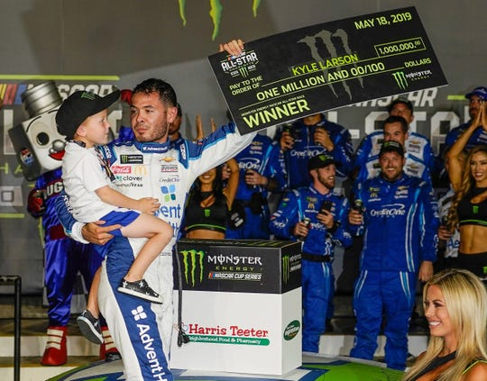 yle Larson (42) celebrates with his son Owen after winning the Monster Energy NASCAR All-Star Race.