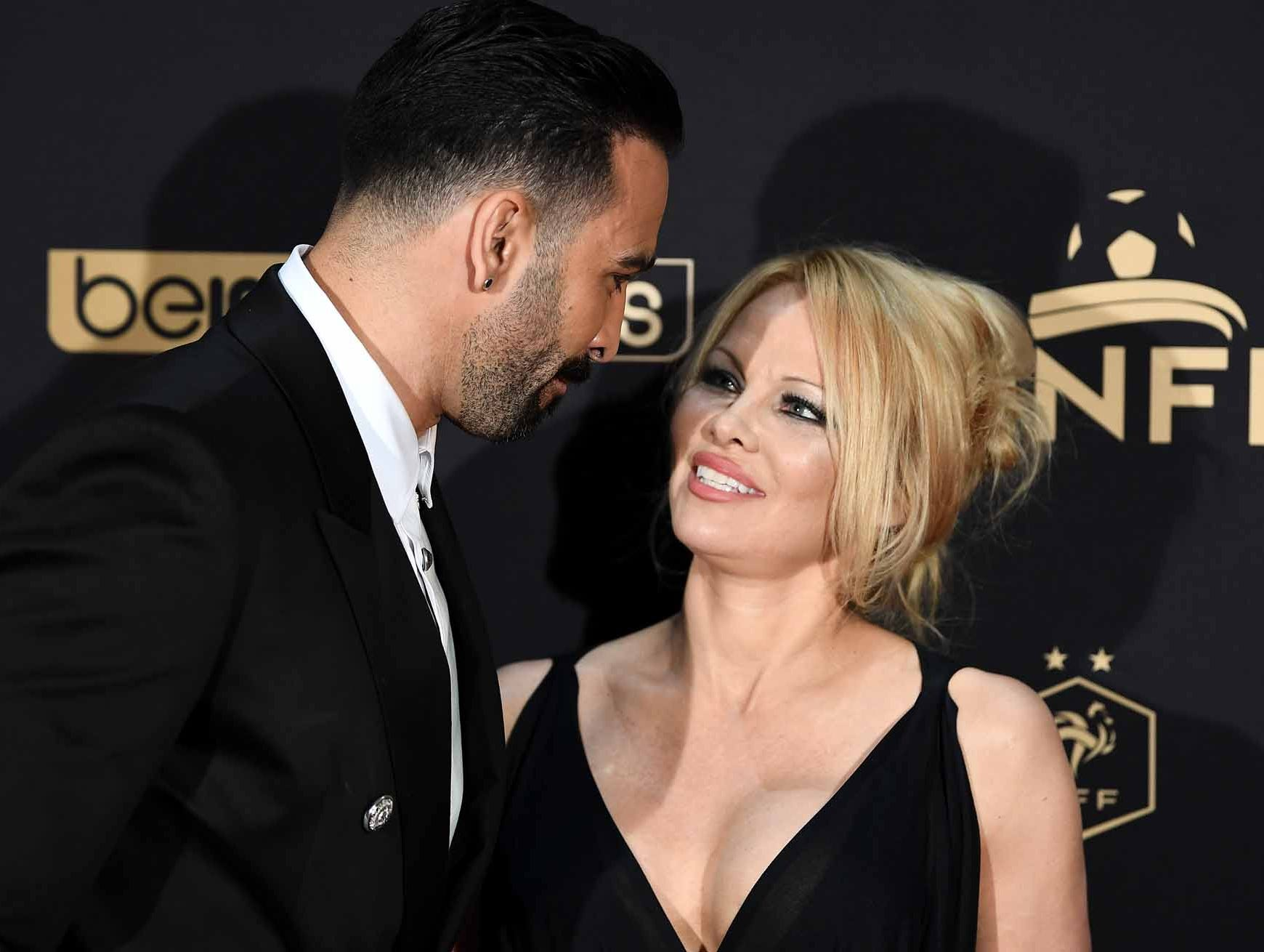 Marseille's defender Adil Rami, left, and Pamela Anderson arrive to take part in a TV show in Paris, as part of the 28th edition of the UNFP (French National Professional Football players Union) trophy ceremony.
