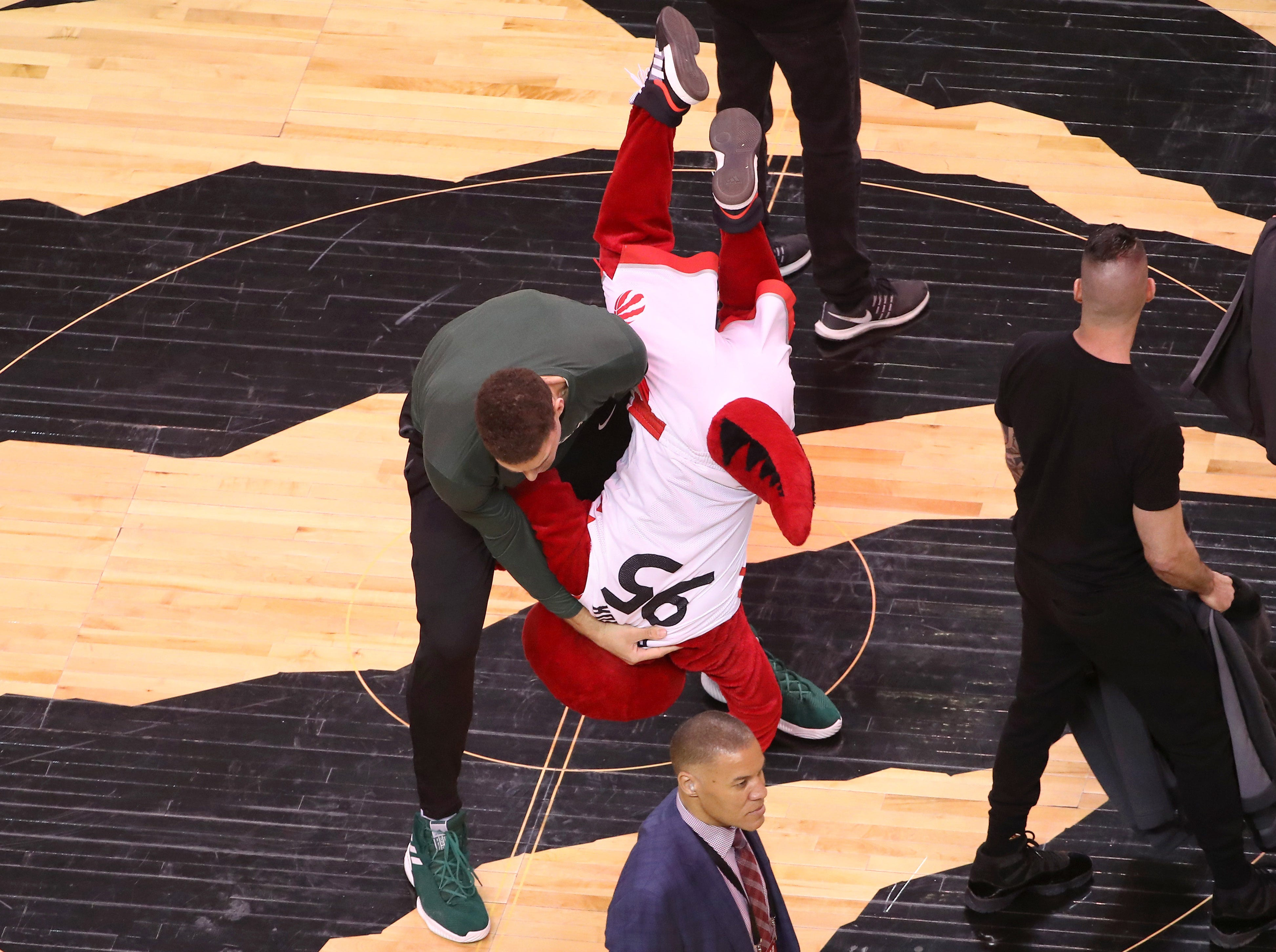 May 19: Milwaukee Bucks center Brook Lopez bodyslams the Toronto Raptors mascot during warm-ups before Game 3.