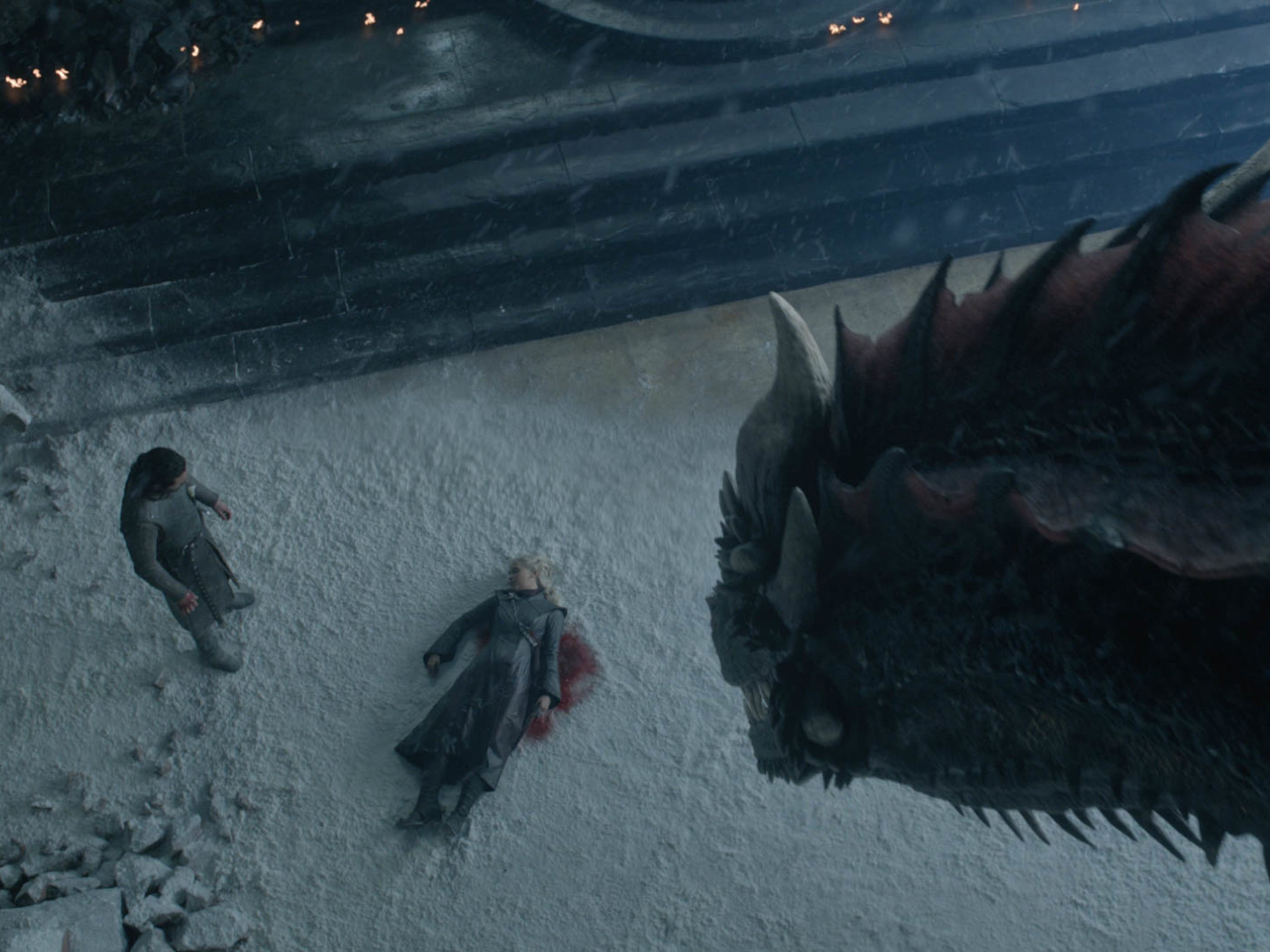 Jon Snow (Kit Harington), left, looks at the lifeless body of Daenerys Targaryen (Emilia Clarke) as her dragon, Drogon, watches.