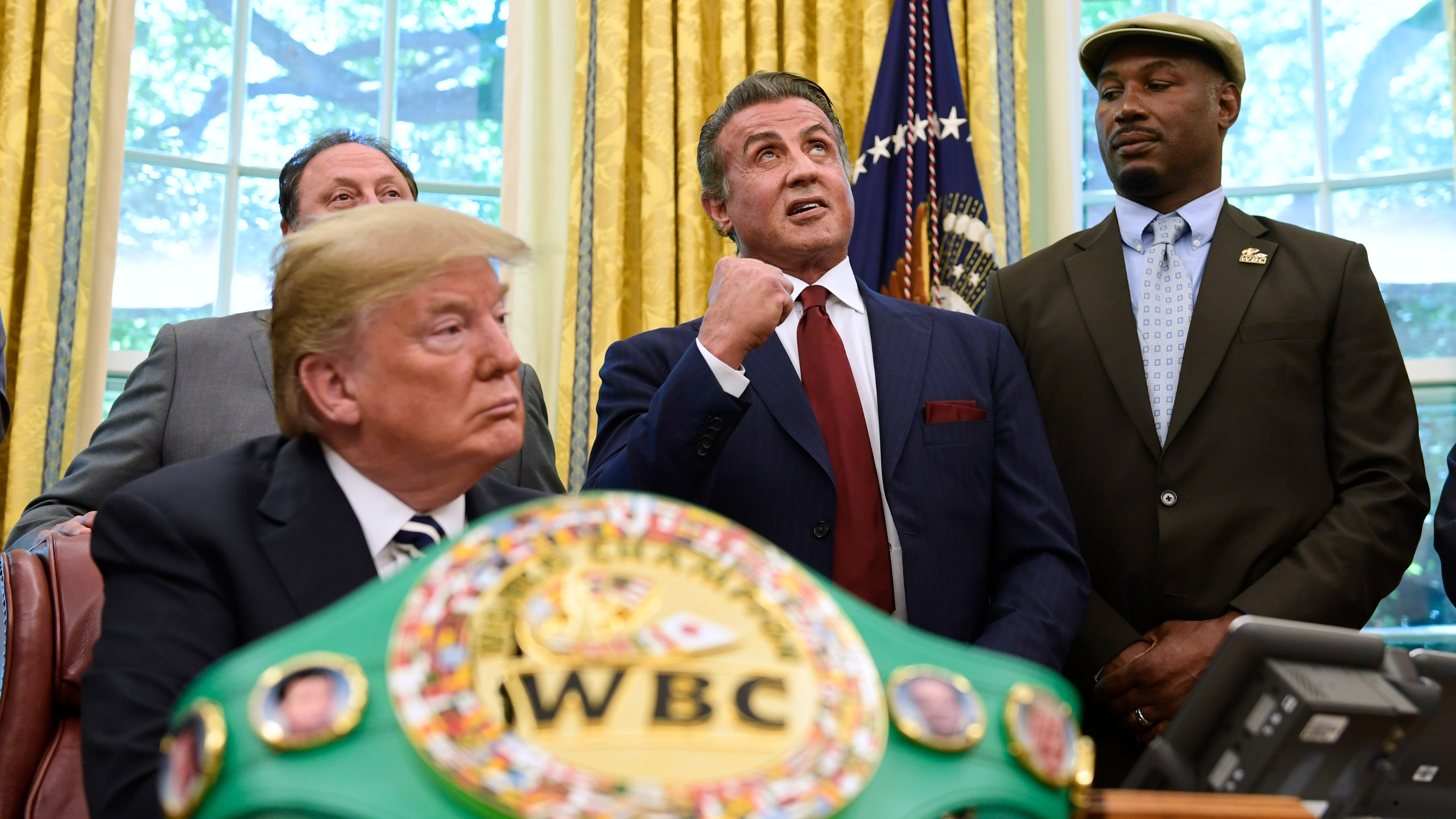 FILE - In this May 24, 2018 file photo, President Donald Trump, left, and heavyweight champion boxer, Lennox Lewis, right, watch as Sylvester Stallone gestures in the Oval Office of the White House in Washington, where Trump granted a posthumous pardon to Jack Johnson, boxing's first black heavyweight champion. Stallone has announced plans for a biopic on the first African American heavyweight champion. (AP Photo/Susan Walsh, File) ORG XMIT: NYET307