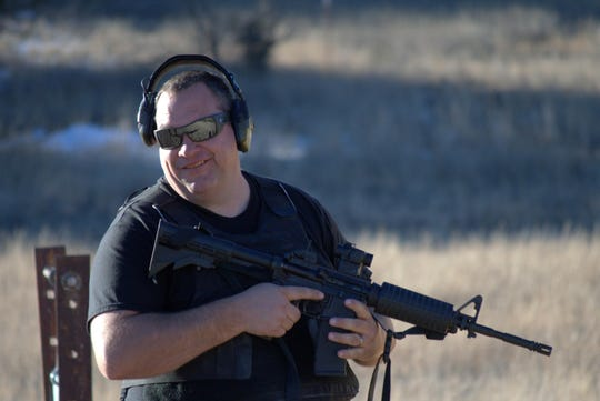 Ian Fletcher, Sheriff, Catron County, New Mexico is a firearms trainer, seen here with an AR-15-type rifle.
