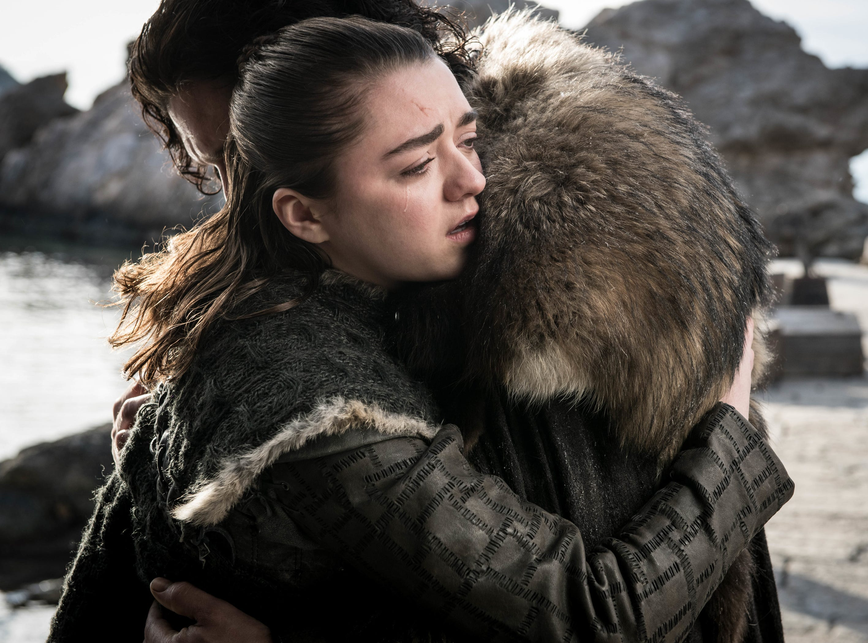 Arya Stark (Maisie Williams), foreground, shares a tearful embrace with Jon Snow (Kit Harington).