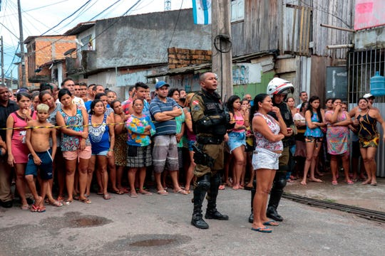 Residents gather outside a bar on Sunday after a shooting left at least 11 people dead in northern Brazil.