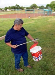 In this May 8, 2019, photo, Hector Aguilar uses a claw grabber extension to remove a hypodermic needle from one of the baseball fields at Atrisco Park.