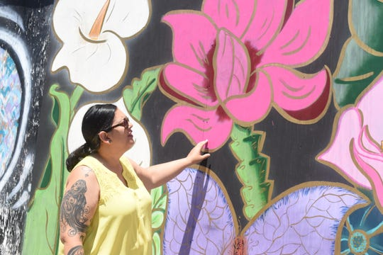 "Artist Liz Cornett looks at the ""garden""wall she and others painted on the plywood covering the old Weiss & Goldring in downtown Alexandria."