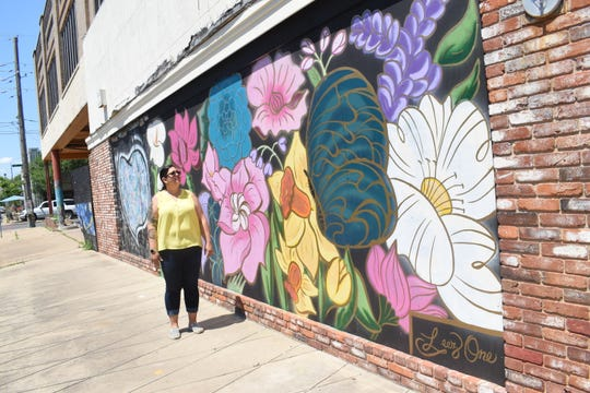 "Artist Liz Cornett looks at the ""garden""wall she and others painted on the plywood covering the old Weiss & Goldring in downtown Alexandria. The original ""hearts"" wall is behind Cornett next to the ""garden"" wall."