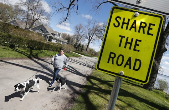 Melissa Schinke of Neenah walks her dogs Blu and Ivy along Lakeshore Avenue in Neenah earlier this year.