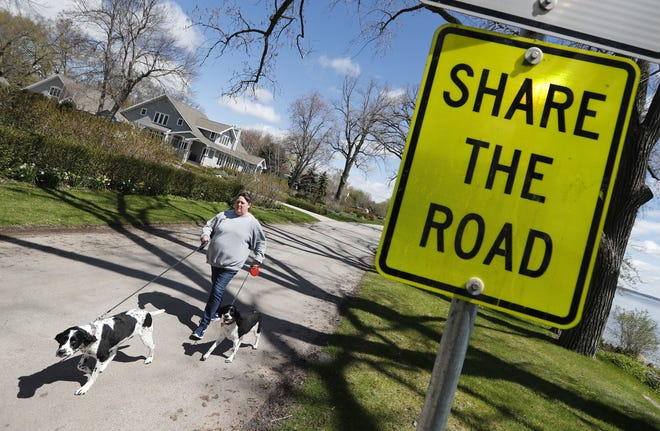 Melissa Schinke of Neenah walks her dogs Blu and Ivy along Lakeshore Avenue in Neenah earlier this year. Mayor Dean Kaufert has proposed to reconstruct the street in 2020.