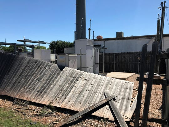 A wooden fence enclosing a cellphone tower behind AM Donuts and Croissants were toppled but the the tower and building were otherwise not damaged in the May 18 Abilene tornado.