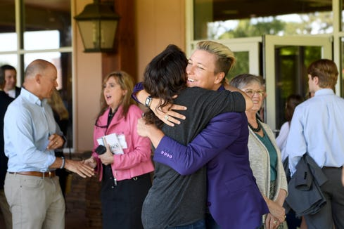 Abby Wambach hugs family friend Katie Kosma before speaking at the 15th annual and final Power of the Purse luncheon at the Crowne Plaza Resort on May 21, 2019.