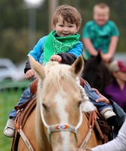 Rowen Morgan, 2, is all smiles as he rides a horse at F.A.R.M. Days at the Kitsap County Fairgrounds on Monday. New volunteers took over the reins of the event this year after the Corey family, who started it over 50 years ago, announced last year it was stepping back from the event.
