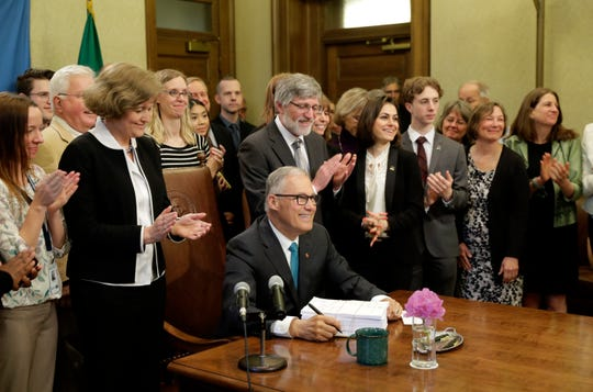 Gov. Jay Inslee, seated center, poses for a photo with lawmakers and others after he signed the state operating budget on Tuesday at the Capitol in Olympia.
