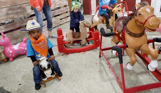 Jaiden Thomas, 2, rides a rocking horse while taking part in F.A.R.M. Days at the Kitsap County Fairgrounds. Children with special needs from around Kitsap County are invited to the annual event that aims to expose them to farm life.