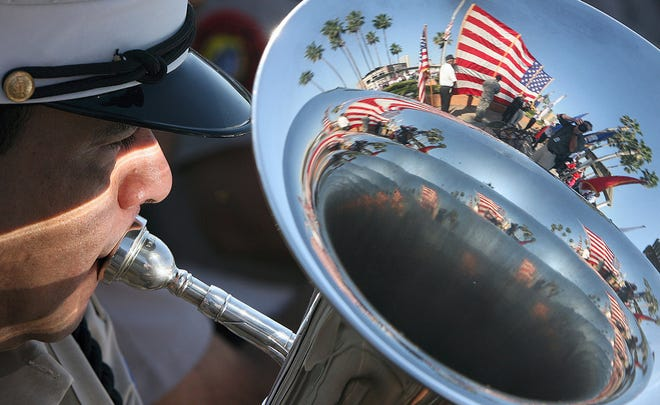 A large American flag reflected in Veterans Band member, Fernando Cruz's, horn during the annual Veterans Day ceremony at Sherill Park in 2009.