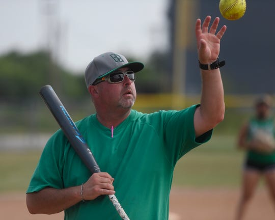 Coach Kevin Hermes catching a softball during practice, Tuesday, May 21, 2019, in Banquete. Hermes is an assistant coach for the team.