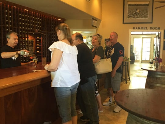 Wine steward Vinny Perrotta (left) serves eight different wines samples to customers at Hawk Haven Vineyard's tasting bar in Rio Grande, Cape May County