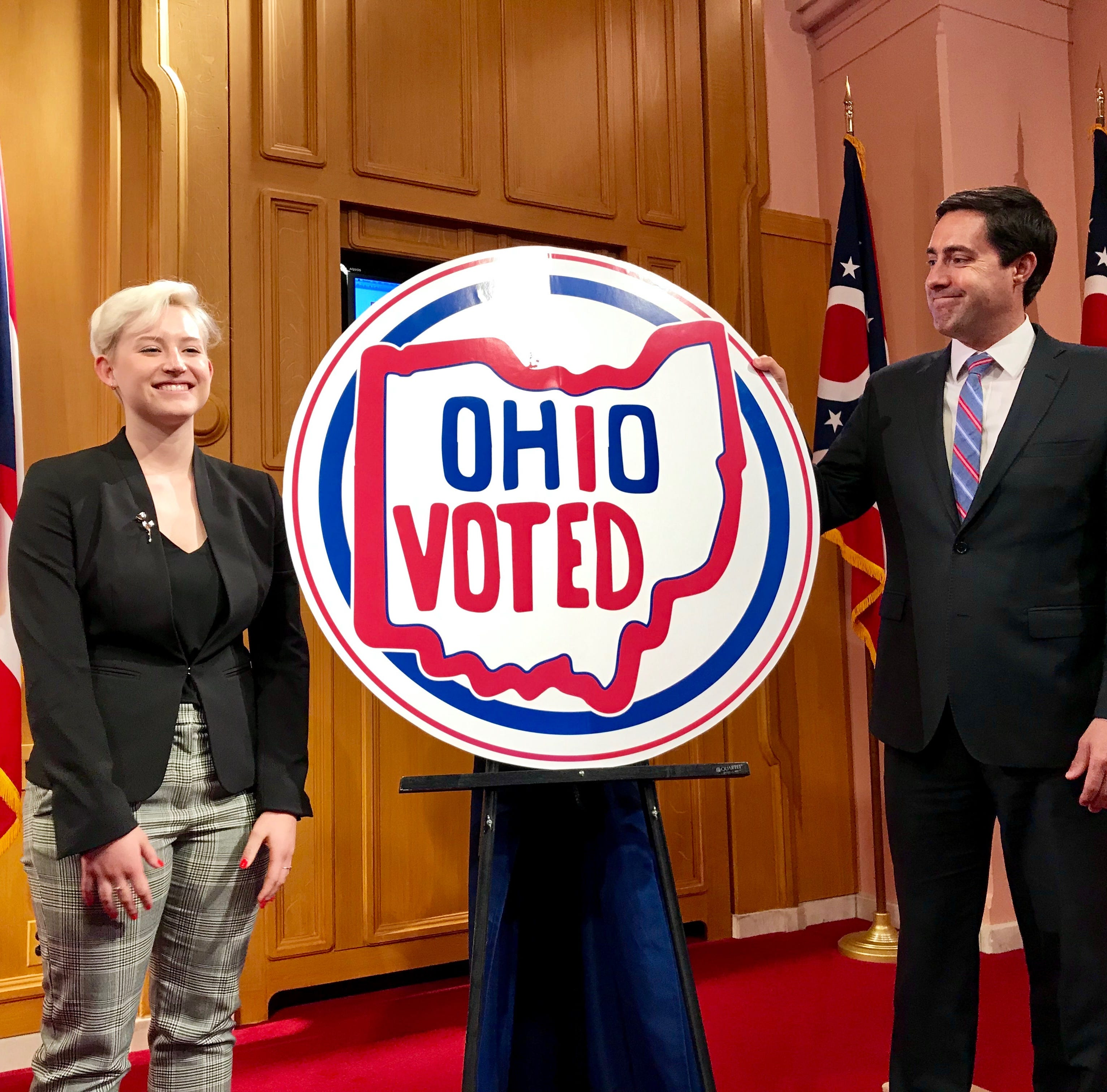 "Emily Legg of Pickaway County stands next to her winning design in Ohio Secretary of State Frank LaRose's contest seeking a new ""I voted"" sticker on May 21, 2019 at the Ohio Statehouse."