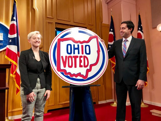 "Emily Legg of Pickaway County stands next to her winning design in Ohio Secretary of State Frank LaRose's contest seeking a new ""I voted"" sticker."