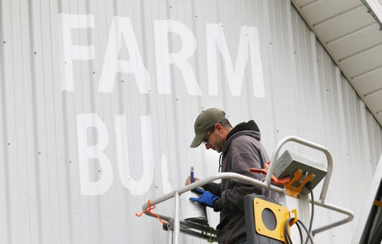 Scott Hagan, known as The Barn Artist, recently painted the Ohio Farm Bureau's centennial logo on a front of one of the Agriculture Buildings at the Coshocton County Fairgrounds.
