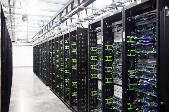 Servers line a data hall in one of Facebook's Altoona data center buildings. The server halls are kept at an optimum temperature between 65 and 85 degrees using filtered air from the outdoors, as well as captured warm air from inside the facility.