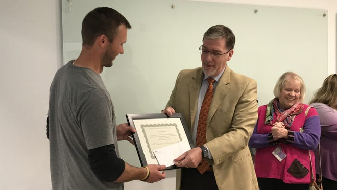 Ankeny teacher Chad Brooks, left, accepts the Professional Educator of the Year award from Bryan Stearns with the Professional Educators of Iowa. Brooks was surprised by staff, student and family members while teaching a class on Tuesday.