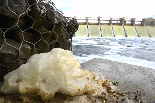 Foam along the Huron River can be seen downstream from the Barton Dam in the Barton Nature Area in Ann Arbor. The state has issued substance advisories against touching foam or eating fish on 18 Michigan waterways due to PFAS chemical exposure concerns.
