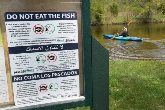 Lori Korte of Novi kayaks  down the Huron River at Proud Lake State Recreation Area in Commerce Township, behind a state health advisory warning people not to eat the fish.