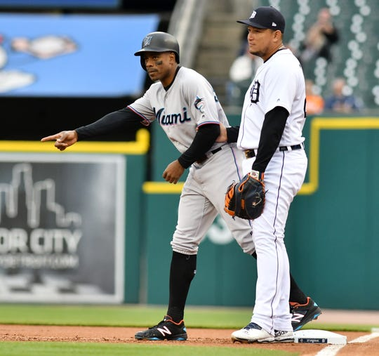 Tigers first baseman Miguel Cabrera jokingly holds the arm of former teammate Marlins' Curtis Granderson in the first inning.