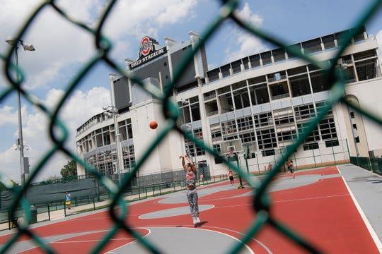 The Ohio State University's football stadium looms above neighboring basketball courts, Saturday, May 18, 2019, in Columbus, Ohio.