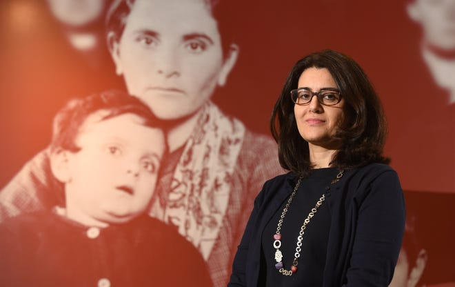Diana Abouali, director of the Arab American National Museum in Dearborn, stands next to an exhibit on migrating to America.  She was born in Toronto to Palestinian parents.