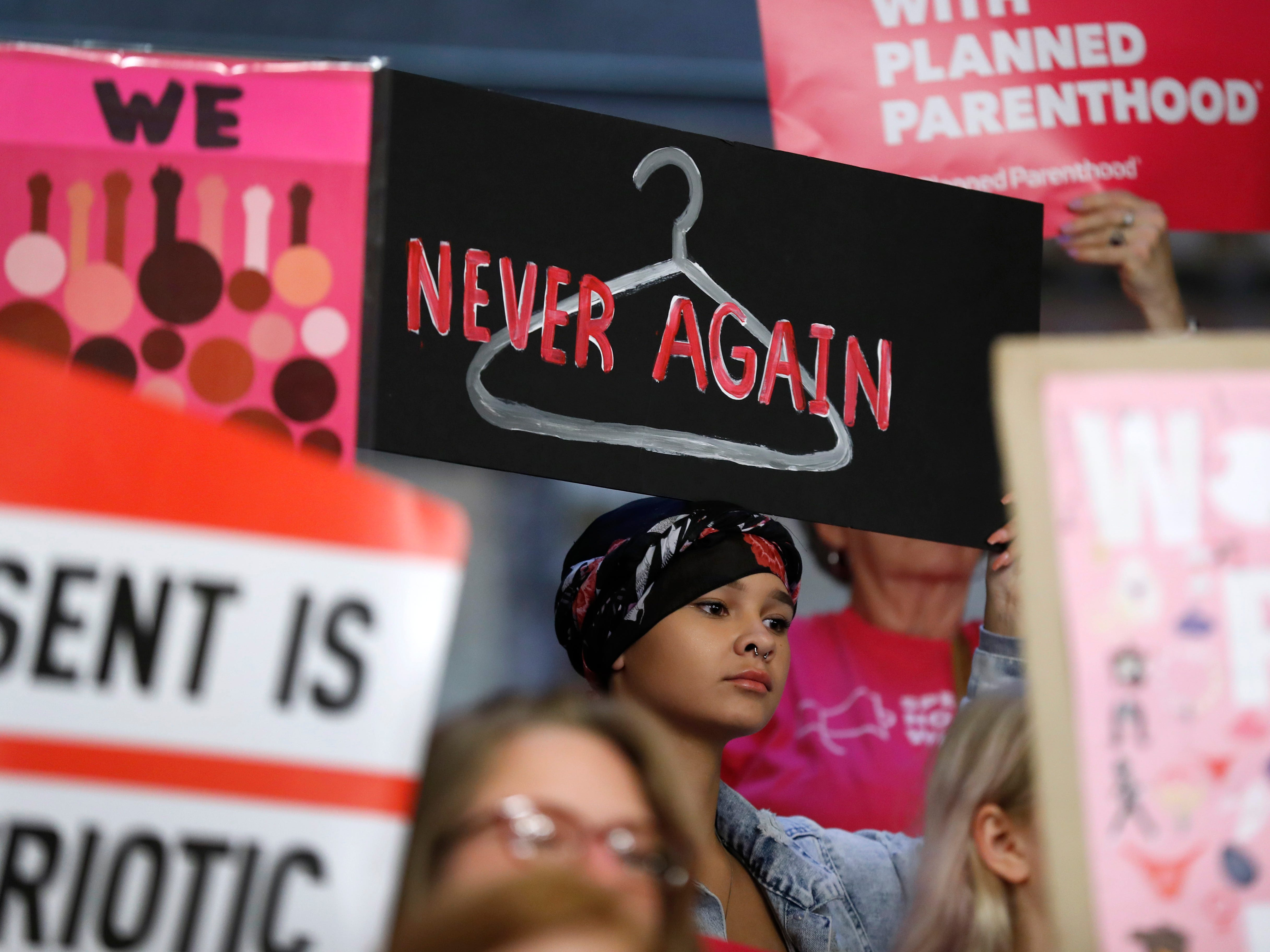 August Mulvihill, of Norwalk, Iowa, center, holds a sign during a rally to protest recent abortion bans, Tuesday, May 21, 2019, at the Statehouse in Des Moines, Iowa.