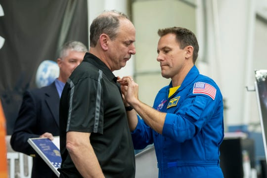 Astronaut Josh Cassada, right, pins a silver Snoopy award onto 40-year employee Matthew Ososky during an event at the Futuramic Tool & Engineering facility in Warren, Tuesday. The award has traveled to space and is given by astronauts to NASA employees and contractors in recognition of their work with flight safety or mission success.