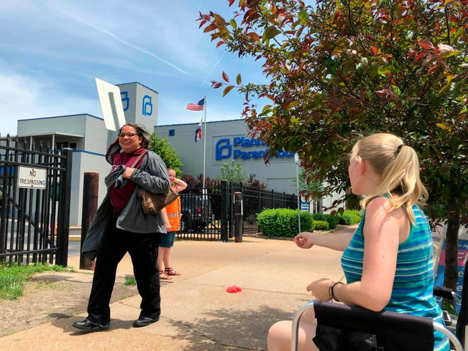 Teresa Pettis, 21, right, greets a passerby outside the Planned Parenthood clinic in St. Louis, Friday, May 17, 2019. Pettis was one of a small number of abortion opponents protesting outside the clinic on the day the Missouri Legislature passed a sweeping measure banning abortions at eight weeks of pregnancy.