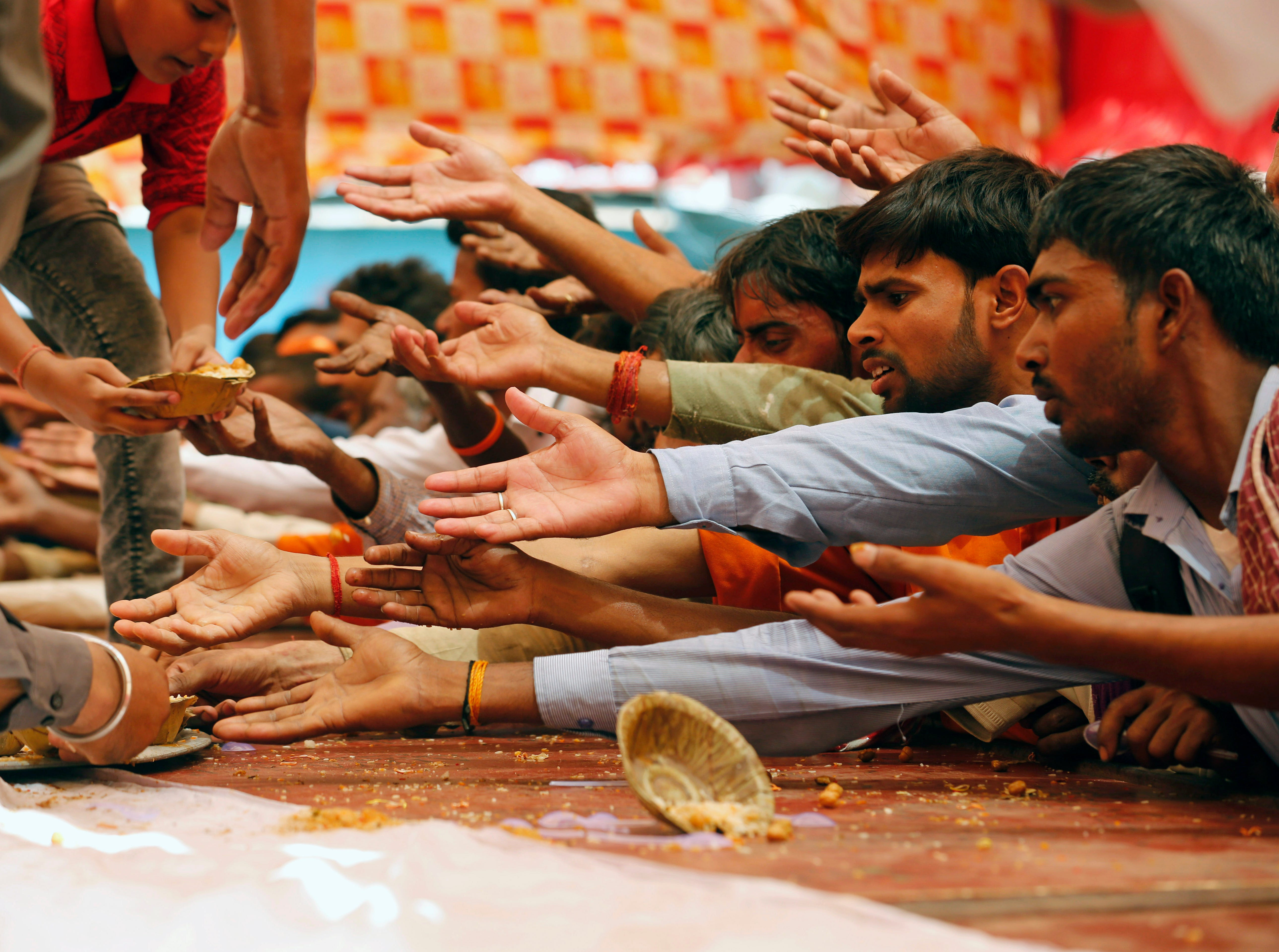 Passersby stretch out their arms to receive food distributed on a street to mark Bada Mangal in Lucknow, India, Tuesday, May 21, 2019. Bada Mangal, celebrated on auspicious Tuesdays, is a day dedicated to Hindu monkey God Hanuman, in which devotees distribute food and drinks to passersby.