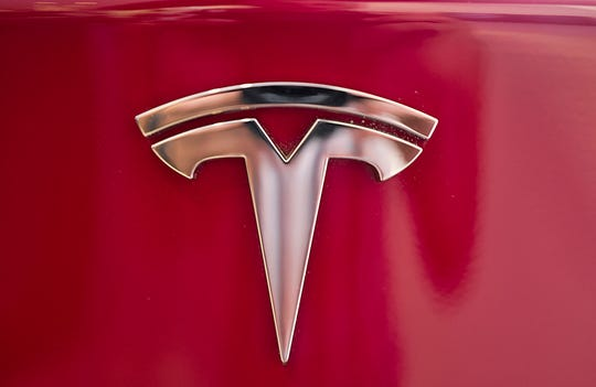 This Wednesday, Aug. 8, 2018, file photo shows the Tesla emblem on the back end of a Model S in the Tesla showroom in Santa Monica, Calif.