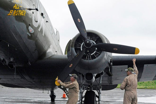 In this April 9, 2019, photo, Pilot Tom Travis, left, and crew member Ray Clausen turn a prop on the World War II troop carrier That's All, Brother during a stop in Birmingham, Ala.