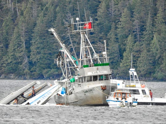 This Monday, May 20, 2019 photo provided by Aerial Leask shows good Samaritans off of fishing vessels attempting to bring in a floatplane that crashed in the harbor of Metlakatla, Alaska. Authorities say a pilot and a single passenger have died after the small plane crashed Monday near Ketchikan.